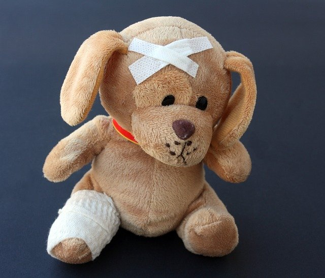 Teddy bear with a bandaged leg and head