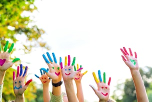 Hands painted in rainbow colours with happy faces